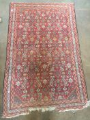 A Herati wool rug The wine red field extensively filled with herati repeat within stylised herati