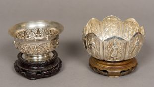 Two Indian white metal bowls Both worked with embossed deities and standing on wooden bases.