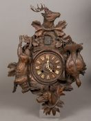 A late 19th century Black Forest carved wooden cuckoo clock The dial with Roman numerals surrounded