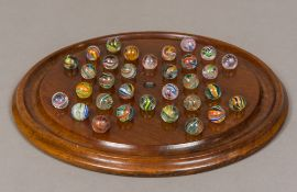 A large mahogany solitaire board Together with a set of hand blown coloured air twist marbles.