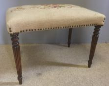 A mahogany framed stool The floral tapestry covered seat supported on gadrooned tapering legs.