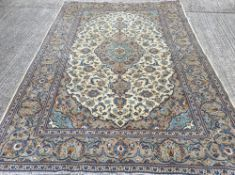 A Kashan wool carpet The ivory field enclosing a central medallion with pendant palmettes within