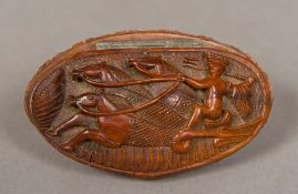 A 19th century carved coquilla nut snuff box The hinged lid decorated with a charioteer. 8 cm long.