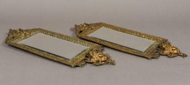 A pair of Victorian cast bronze wall glasses Each surmounted with a male mask above the bevelled