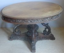 A 19th century Anglo-Indian padouk tilt-top centre table The lappet carved hinged oval top above