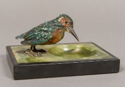 An early 20th century onyx and black slate pin tray Surmounted with a cold painted bronze model of