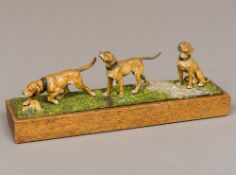 A cold painted bronze group of three working dogs in various poses On a naturalistic cast base,