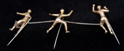 A set of three unmarked gold stick pins Each formed as a mountaineer, linked by a chain.