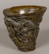 A Chinese libation cup Typically decorated in the round with various figures and a pagoda in a tree