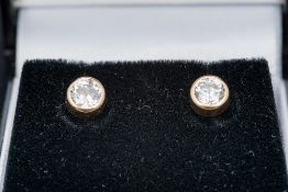 A pair of unmarked gold diamond set ear studs Each rub over set stone approximately 0.30 carat.