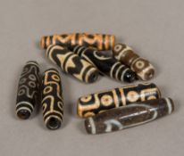 Eight Tibetan agate Dzi beads Each of barrel form with typical decoration. Each approximately 5.