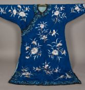 A Chinese embroidered silk robe Worked with floral sprays on a blue ground.