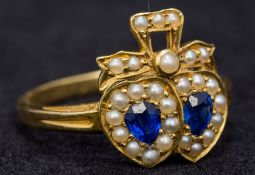 A Victorian 18 ct gold sapphire and seed pearl ring Of bow tied double heart form. 1.3 cm high.