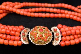 An unmarked 18 ct gold mounted coral bea