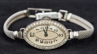 A 9 ct white gold cased diamond set cocktail watch The oval silvered dial with Arabic numerals,