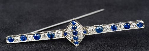 An Art Deco platinum, diamond and sapphire set bar brooch Centrally set with a stone filled lozenge.