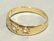 An 18 ct gold three stone diamond gypsy set ring