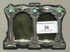 A small silver Art Nouveau style double photograph frame