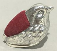 A silver pin cushion in the form of a chick