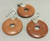 A silver and goldstone pendant and earrings