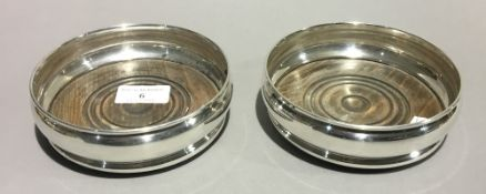 A pair of silver bottle coasters