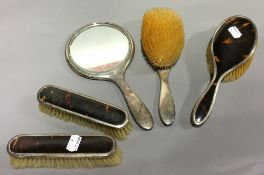 A silver mounted tortoiseshell dressing table set, comprising: two clothes brushes,