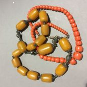 A large bead necklace and a red bead necklace