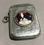 A silver vesta decorated with a dog