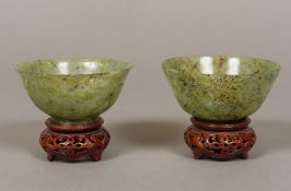 A pair of Chinese carved green and russet jade bowlsm standing on carved and pierced wood bases.