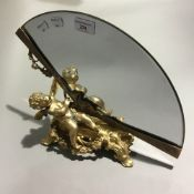 A fan shaped mirror mounted on a cherub form base