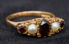 A 9 ct gold ruby and seed pearl set ring (size T/U, approximately 4 grammes all in).