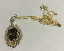 A 9 ct gold smoky quartz pendant and chain (3.