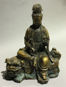 A bronze model of Guanyin on a dog-of-fo