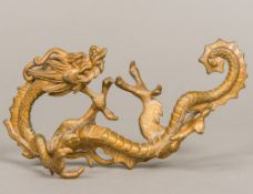 A 19th century Chinese gilt bronze brush rest Formed as a scrolling dragon. 18 cm long.