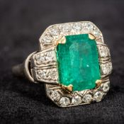 An unmarked white gold or platinum emerald and diamond ring The central claw set emerald bordered