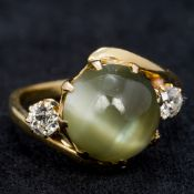 An 18 ct gold chrysoberyl cats eye and diamond cross over ring The two diamonds totalling