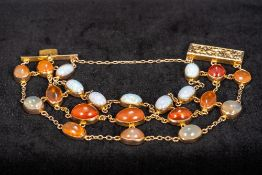 A 9 ct gold cabochon stone set bracelet Including opals and moonstones. Approximately 18 cm long.