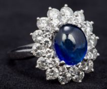 A 9 ct white gold diamond cluster ring - WITHDRAWN Centred with a synthetic corundum cabochon.