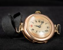 An early 20th century 9 ct gold cased Rolex wristwatch The champagne dial with batons. 3 cm wide.