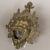 A Tibetan bronze mask Formed as an open mouthed deity with pierced headdress. 35 cm high.