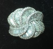An 18 ct white gold diamond set ring The baguette and round cut stones worked in a stylised swirl.