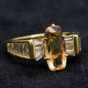 An 18 ct gold diamond and imperial topaz ring With central claw set topaz flanked by baguette cut