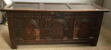 An 18th century carved oak coffer The hinged rectangular three panelled lid above the arch carved