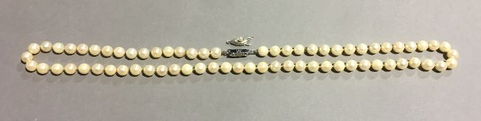 A single strand Sakata Ltd pearl necklace 62 cm long.