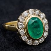An 18 ct gold diamond and emerald cluster ring The central emerald flanked by a row of diamonds