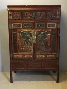 A late 19th century Chinese carved wooden cabinet on stand The top section with two small doors and