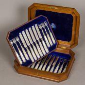 A Victorian burr walnut cased set of twelve mother-of-pearl handled silver dessert knives and forks,