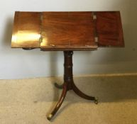 A George III mahogany music stand The twin hinged adjustable top above two fold-out candle stands,