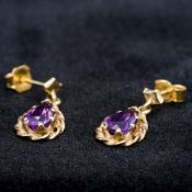 A pair of 9 ct gold amethyst set earrings Each of drop form. Each 1.7 cm high.