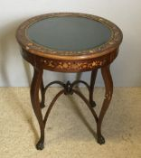 An Edwardian inlaid mahogany bijouterie table The hinged double glazed circular top with a border